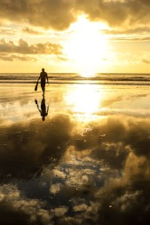 A gentleman walks in from the ocean as the sun creates a silhouette.