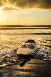 A surfboard lays on the shore.