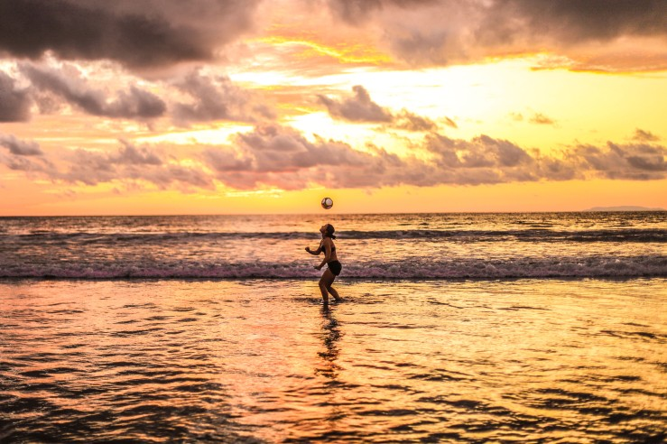 Juggling the soccer ball, the woman stays in the water for a brief moment before leaving.