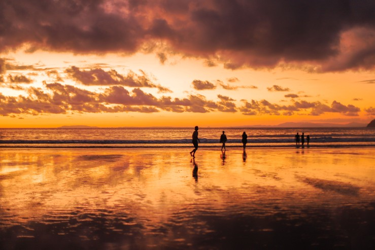 After the sunset, people remain on the beach to play and walk. The sun has left a gorgeous orange and pink saturated sky.